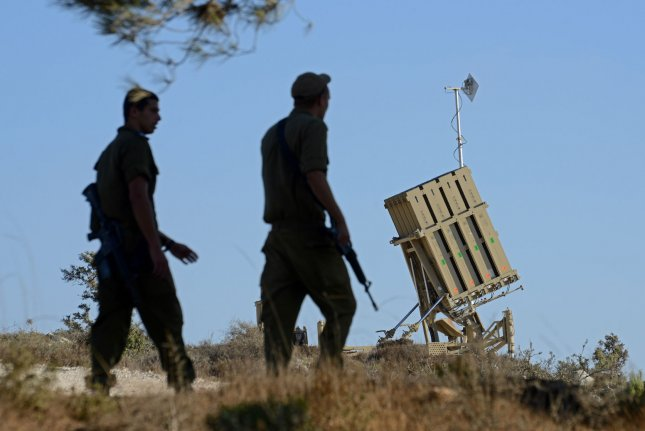 Israeli soldiers walk near an Iron Dome anti-missile defense battery on the outskirts of Jerusalem, Israel, September 9, 2013. The Iron Dome is designed to intercept and destroy incoming rockets and artillery shells. Israel is concerned that Syria could launch missiles at Israel if the United States attacks Syria over alleged use of chemical weapons against civilians. UPI/Debbie Hill
