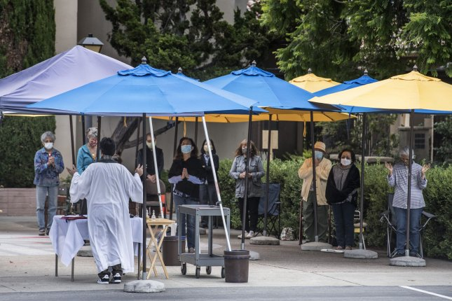 A priest conducts mass outdoors due to the COVID-19 pandemic, in Cupertino, Calif., on August 5. Photo by Terry Schmitt/UPI