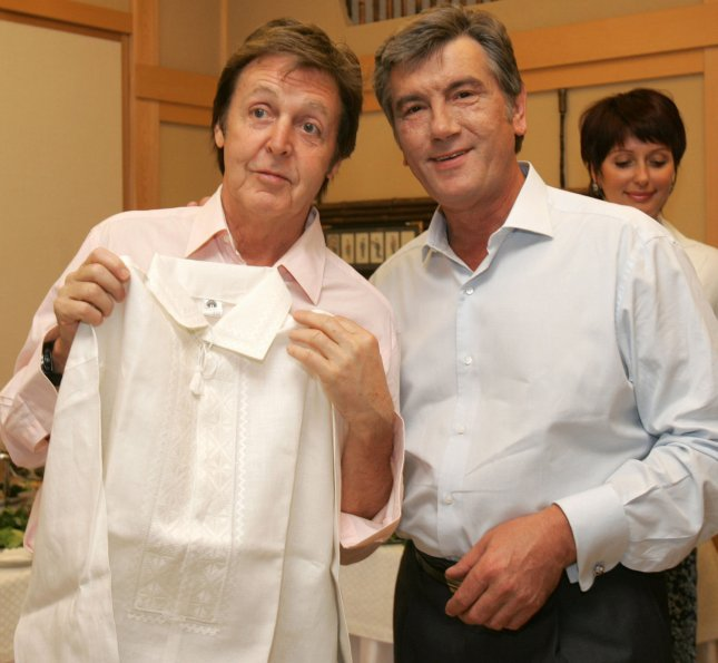 British musician Paul McCartney (L) holds up a shirt which he received from Ukrainian President Viktor Yushchenko (R) during their meeting in Kiev on June 15, 2008. (UPI Photo/Mykhailo Markiv/Pool)