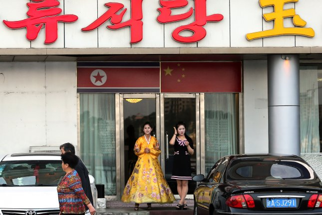 A North Korean woman and hostess stand outside a North Korean restaurant waiting for customers in Dandong, China's largest border city with North Korea. A South Korean analyst said grassroots enterprises in North Korea have increased, and businesses are diversifying. Photo by Stephen Shaver/UPI