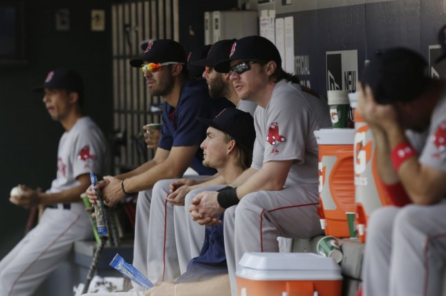 Players in the Boston Red Sox dug out watch the game. Photo by John Angelillo/UPI