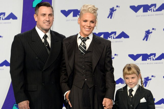 Carey Hart (L), pictured with Pink (C) and daughter Willow, poked the parent police by sharing a video of Willow using a gun. File Photo by Jim Ruymen/UPI