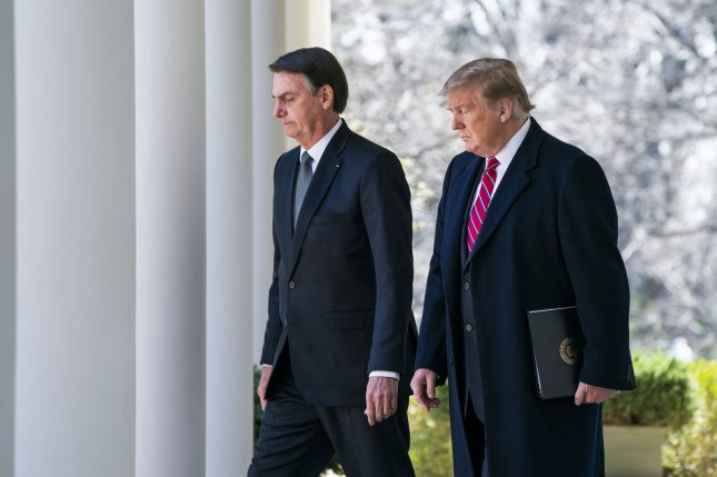 U.S. President Donald Trump walks with Brazilian President Jair Bolsonaro along the West Colonnade of the White House on March 19 before a joint news conference in the Rose Garden. File Photo by Jim Lo Scalzo/UPI