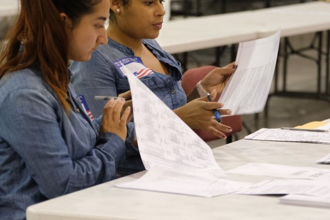 Palm Beach County election workers check ballots during a machine recount for two gubernatorial and senate races. Photo by Gary I Rothstein/UPI