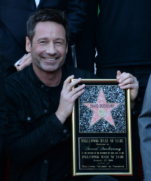 David Duchovny holds a replica plaque during an unveiling ceremony honoring him with the 2,572nd star on the Hollywood Walk of Fame in Los Angeles on January 25, 2016. The actor turns 60 on August 7. File Photo by Jim Ruymen/UPI