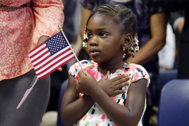 Fatoumata Sangary puts a hand on her heart when her mom becomes a citizen of the United States at a naturalization ceremony for 150 immigrants in New York City on July 2, 2013. Photo: UPI/John Angelillo