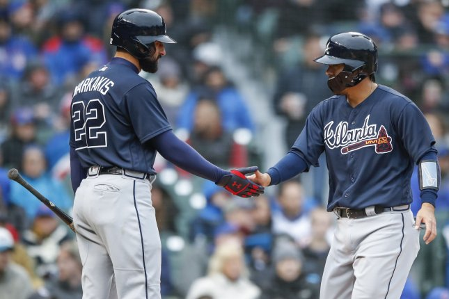 Atlanta Braves catcher Kurt Suzuki (R) celebrates with Atlanta Braves right fielder Nick Markakis (L) after scoring against the Chicago Cubs in the fifth inning of a baseball game on April 13 at Wrigley Field in Chicago, Ill. Photo by Kamil Krzaczynski/UPI