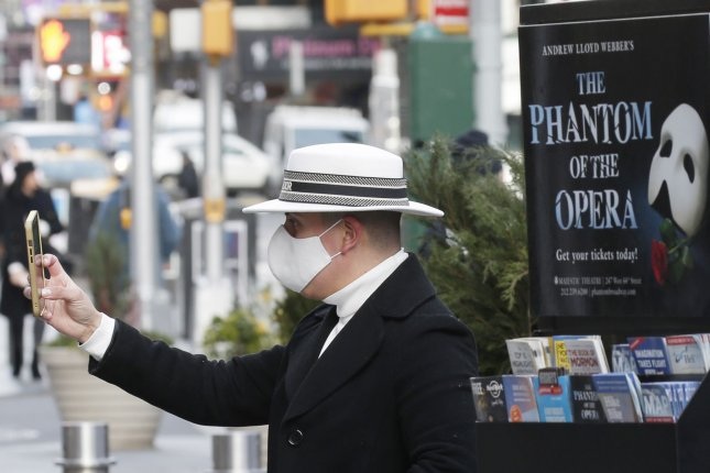 A man takes a photo near a poster for the Broadway show Phantom of the Opera as Times Square remains quiet of pedestrian and automobile traffic due to the coronavirus pandemic in New York City on Monday. Photo by John Angelillo/UPI