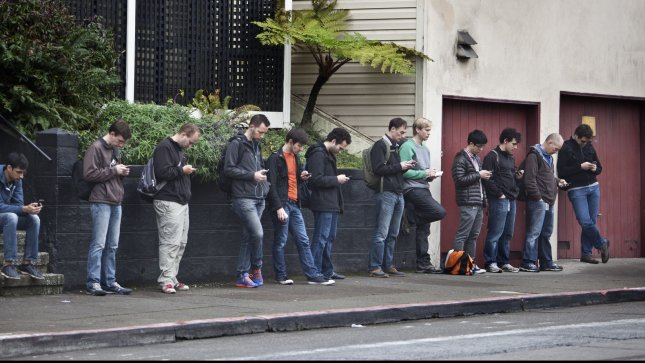 A dozen tech workers check their smart phones as they wait for a bus to take them to Silicon Valley on January 24, 2013 in San Francisco.UPI/Terry Schmitt
