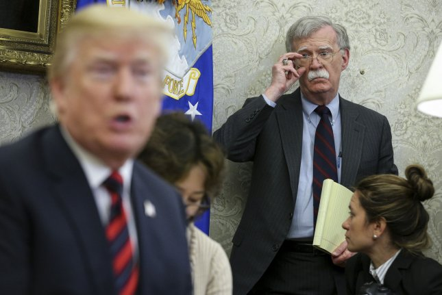 President Donald Trump speaks in the Oval Office of the White House as national security adviser John Bolton listens. File Photo by Oliver Contreras/UPI