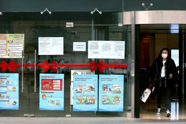 A Chinese worker leaves an office building covered with health warnings due to the threat of the new coronavirus in Beijing on Monday. Photo by Stephen Shaver/UPI