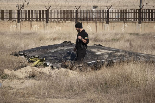 An official walks amid wreckage from a Ukrainian Boeing 737 about 30 miles south of Tehran on Wednesday. Photo by Morteza Nikoubazi/UPI