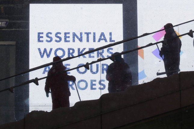 Masked workers shovel snow off of steps and surfaces in New York City's Times Square last Thursday, in front of a sign that honors front-line health workers and other essential workers as heroes. Photo by John Angelillo/UPI