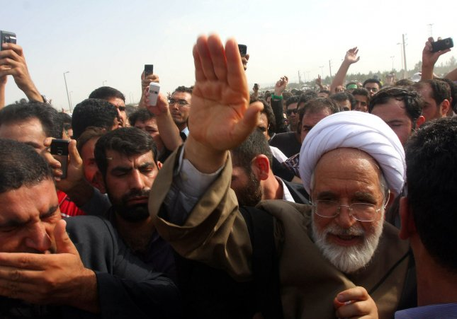 Iranian opposition leader Mehdi Karroubi (R) waves among his supporters. Karroubi has been missing since July 16, 2011. UPI