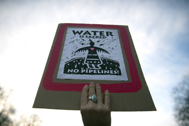 A protester holds a sign during a demonstration against the Dakota Access Pipeline near the White House in Washington, D.C. on February 8. The pipeline leaked about 84 gallons of oil in South Dakota in April, but the leak wasn't noticed until Tuesday. File Photo by Kevin Dietsch/UPI
