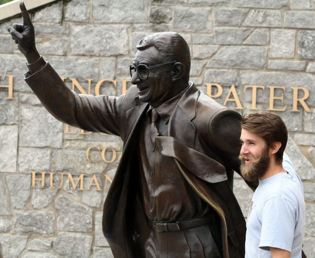 A man poses with the Joe Paterno statue outside Beaver Stadium in State College, Pa. Photo by George M Powers/UPI