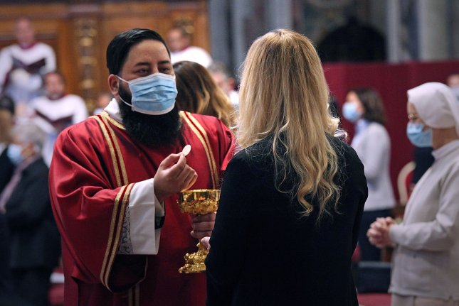A deacon gives communion to a nun during a Pentacost mass celebrated by Pope Francis in St. Peter's Basilica at the Vatican in 2020. File Pool Photo by Siciliani/Spaziani/UPI