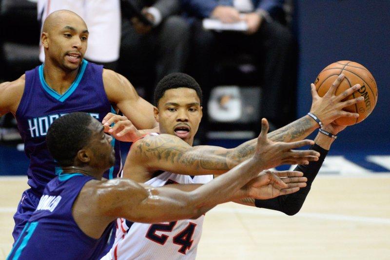 Atlanta Hawks' Kent Bazemore (24) passes under pressure from Charlotte Hornets' Gerald Henderson (L) and Noah Vonleh (11). UPI/David Tulis