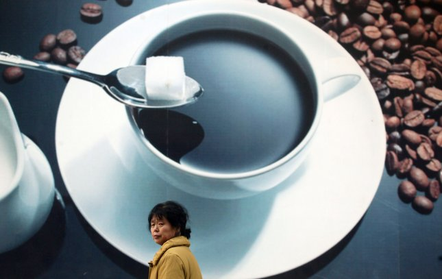A Chinese woman walks past a giant coffee shop advertisement in downtown Beijing February 07, 2009. In tea-loving China, having a cup of coffee in a gourmet coffee lounge is fast becoming a symbol of status for the young and affluent in the cities. (UPI Photo/Stephen Shaver)