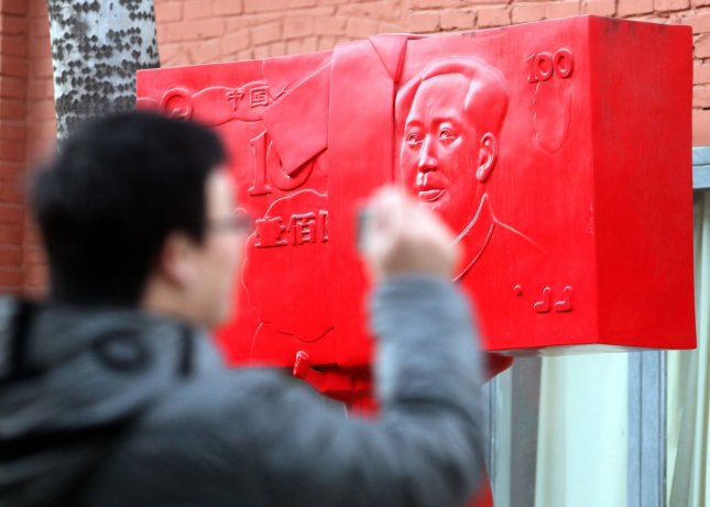 A Chinese man takes a photo of an art installation piece described as 'socialist workers upholding the strength of China's wealth' placed on a sidewalk in an international art zone in Beijing December 5, 2010. The Chinese yuan rose to a new hight against the U.S. dollar this year, taking a first step toward greater flexibility the Chinese central bank promised when it eased the currency's peg in recent months. UPI/Stephen Shaver