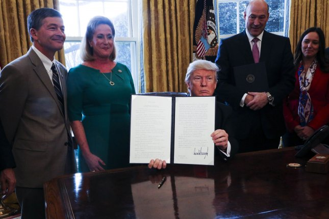 U.S. President Donald Trump signs Executive Orders in the Oval Office of the White House, including an order to review the Dodd-Frank Wall Street Reform and Consumer Protection Act to start to roll back financial regulations of the Obama era, in Washington, DC on February 3, 2017. Pool Photo by Aude Guerrucci/UPI