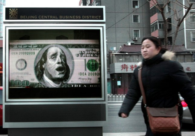 A Chinese woman walks past a television billboard, featuring a distressed Benjamin Franklin on a USD100 bill, in downtown Beijing on December 08, 2009. China has expressed concern about its huge stock of U.S. Treasury securities, Chinese Premier Wen Jiabo recently said. Beijing has become increasingly vocal about what it sees as U.S. economic mismanagement making U.S. investments riskier. UPI/Stephen Shaver