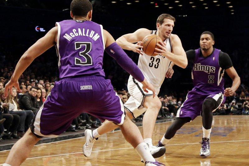 Brooklyn Nets' Mirza Teletovic drives the basketball between Sacramento Kings' Ray McCallum and Rudy Gay. UPI/John Angelillo