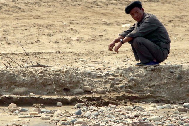 A North Korean waits with his tractor for a small pontoon to cross a tributary on the banks of the Yalu River near Sinuiju, across the Yalu River from Dandong, China's largest border city with North Korea. Life under Kim Jong Un has declined, according to a recent South Korean survey. File Photo by Stephen Shaver
