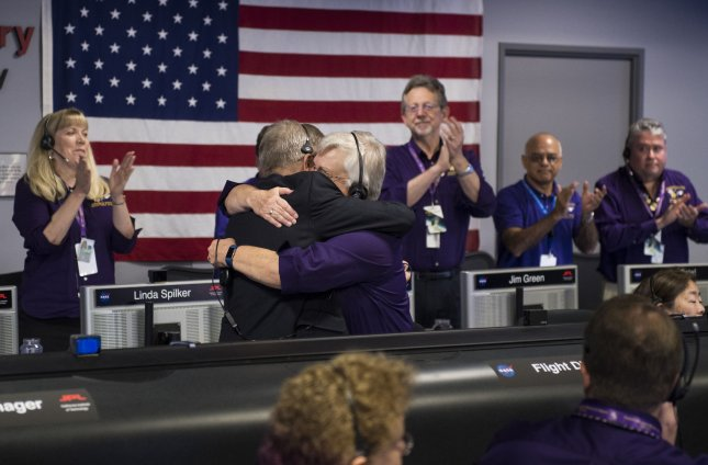 Cassini program manager at JPL, Earl Maize (L), and spacecraft operations team manager for the Cassini mission at Saturn, Julie Webster (R), embrace at NASA's Jet Propulsion Laboratory in Pasadena, Calif., after the Cassini spacecraft plunged into Saturn on Friday. Photo by Joel Kowski/NASA/UPI