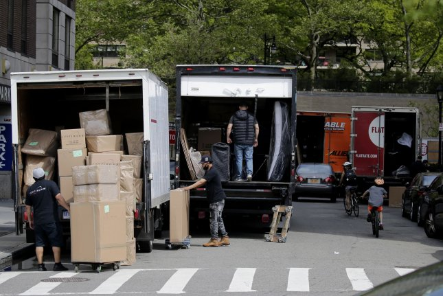 Moving trucks and workers are seen on a street on New York City's Upper West Side on May 27, 2020, not long after Gov. Andrew Cuomo announced an extension for a moratorium than bans landlords from evicting tenants with coronavirus-related hardship. File Photo by John Angelillo/UPI