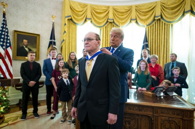 President Donald Trump presents the Presidential Medal of Freedom to Dan Gable in the Oval Office of the White House on Monday. Photo by Doug Mills/UPI/Pool