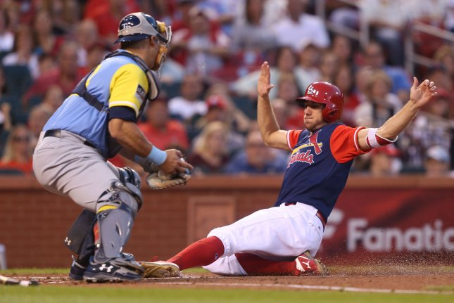 St. Louis Cardinals' Stephen Piscotty slides safely into home plate before the tag by Tampa Bay Rays catcher Wilson Ramos. File photo by Bill Greenblatt/UPI