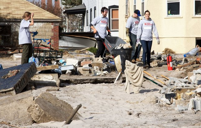People help clean up one of the storm-damaged homes following Hurricane Sandy in the Belle Harbor section in the borough of Queens on November 6, 2012 in New York City. UPI /Monika Graff
