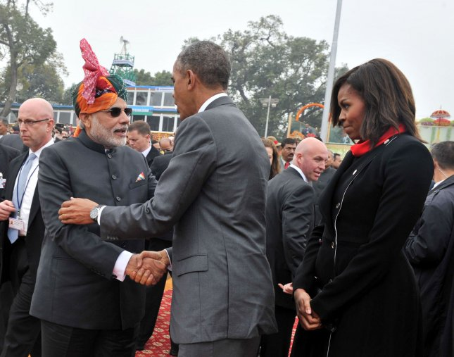 India's Prime Minister Shri Narendra Modi (L) shakes hands with U.S. President Barack Obama as First Lady Michelle Obama looks on during the 66th Republic Day Parade on the Raj Path in New Delhi, India on January 26, 2015. UPI