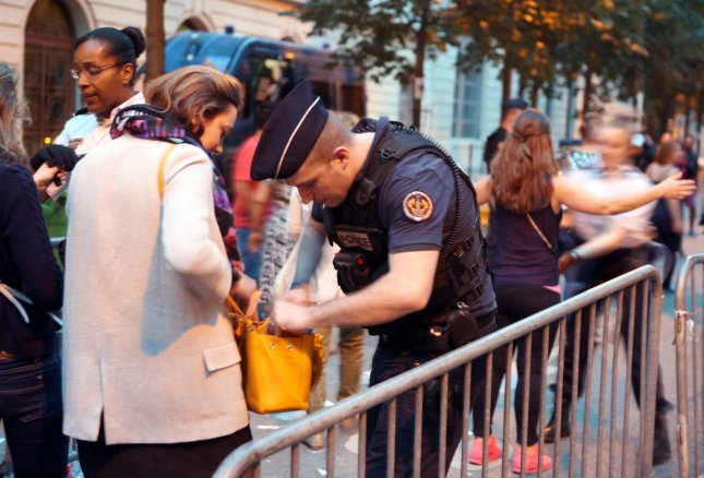 Soccer fans are checked by police before being allowed into the fan zone at the foot of the Eiffel Tower in Paris June11, 2016. Two terrorist suspects were arrested in Brussels Sunday suspected of planning an attack on the soccer fan zone there. Photo by Maya Vidon-White/UPI