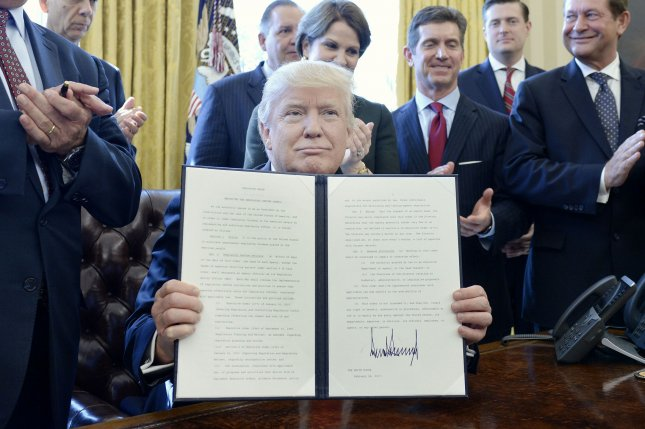 U.S. President Donald Trump, flanked by business leaders, shows an executive order establishing regulatory reform officers and task forces in US agencies in the Oval Office of the White House on February 24 in Washington, DC. Poll results released Sunday showed 44 percent of Americans approve of the job Trump is doing. Pool photo by Olivier Douliery/UPI