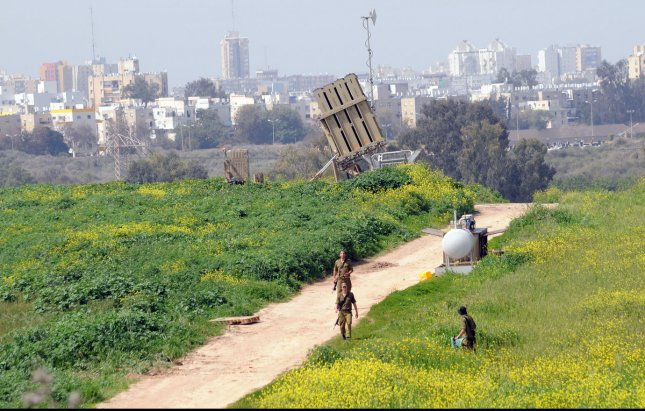 Israeli soldiers walk near the Israeli anti-missile system known as Iron Dome, used to intercept rockets fired by Palestinian militants from the Gaza Strip, in Ashdod, Israel, March 11, 2012. More than 120 rockets have been fired at Israel from Gaza since Friday, while the Iron Dome system has intercepted more than 30 rockets. The deadliest clashes between the two sides in over a year have entered their third day showing no signs of subsiding. UPI/Debbie Hill