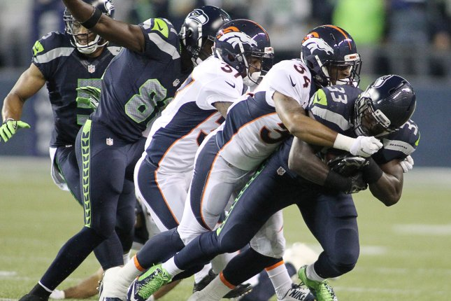 Seattle Seahawks running back Christine Michael (33) is brought down by Denver Broncos Lorenxo Doss (37)and Ross Madison (34) during the quarter at CenturyLink Field on August 14, 2015 in Seattle Washington. The Broncos beat the Seahawks 22-20. Photo by Jim Bryant/UPI