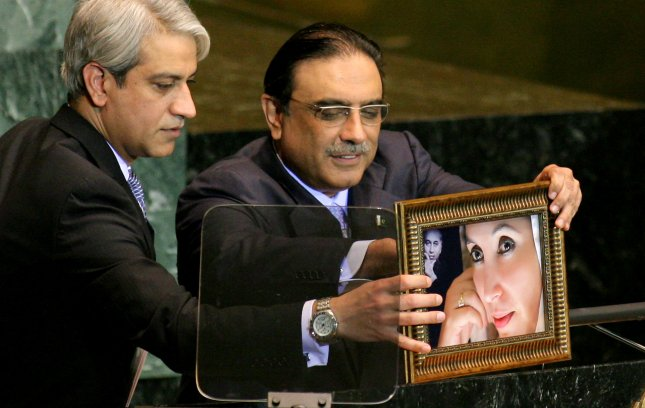 Pakistani President Asif Ali Zardi (R) is assisted as he places a portrait of his assassinated wife Benazir Bhutto onto the podium before addressing the 64th General Assembly at the United Nations on September 25, 2009 in New York City. UPI /Monika Graff