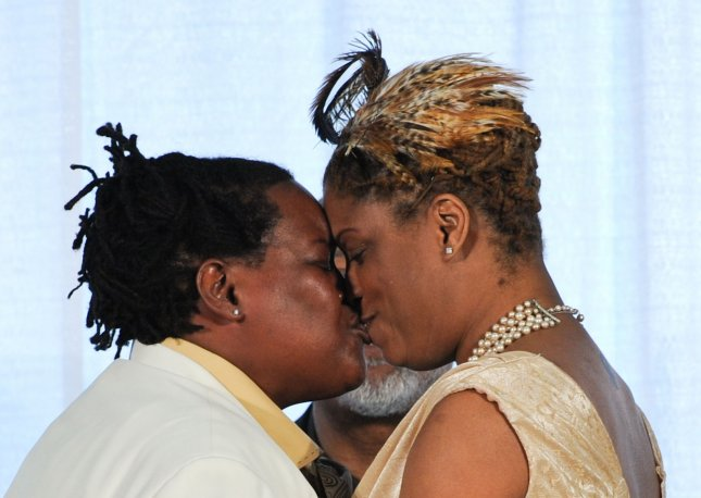 Angelisa Young (R) and Sinjolya Townsend, the first gay couple to wed in the District of Columbia, kiss after they exchanged vows at their wedding ceremony at the Human Rights Campaign building in Washington on March 9, 2010. In December 2009, the DC Council approved a bill that would allow for same-sex marriages to be performed in the District. Americans estimate 25 percent of the population is gay. UPI/Alexis C. Glenn