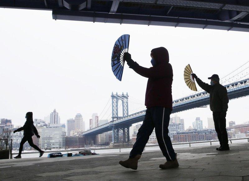 Небольшая группа людей исполняет танец с китайскими бумажными веерами под диском FDR с видом на Манхэттенский мост в Нью-Йорке в феврале. В докладе, опубликованном в начале марта, говорится, что в Нью-Йорке наблюдался резкий рост антиазиатских инцидентов ненависти в 2020 году. Фото: John Angelillo/UPI
