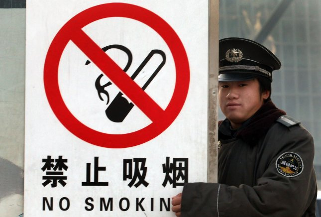 A Chinese security guard stands next to a No smoking sign posted on a construction site in Beijing November 28, 2010. Smoking could eventually kill a third of all young Chinese men if nothing is done to get them to drop the habit, according to the largest-to-date survey of tobacco use in the country. Two recent landmark studies involving 1.25 million Chinese people show that China has the largest number of smoking-related deaths in the world. UPI/Stephen Shaver