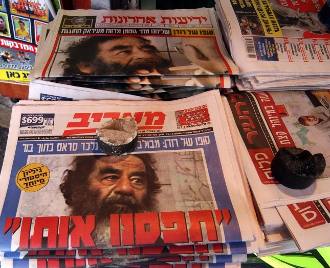 Israeli newspapers with cover photos of US captured, former Iraqi ruler, Saddam Hussein at a news stand in Jerusalem, December 15, 2003. Saddam hurled 39 scud missiles on Israel in 1991 during the Gulf War. Photo by Debbie Hill/UPI