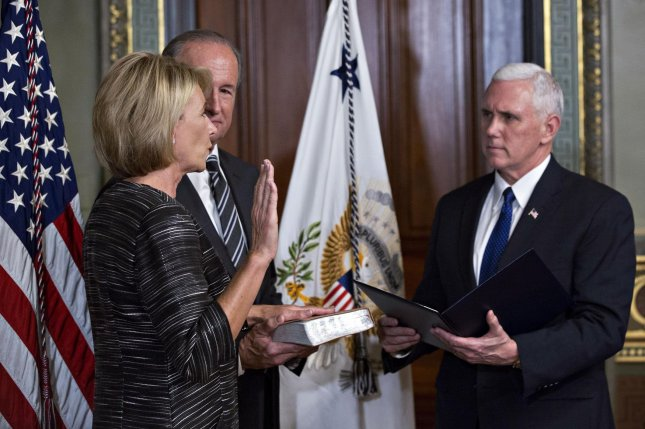 Vice President Mike Pence, right, swears in Betsy DeVos as U.S. secretary of education, as husband Dick DeVos Jr., looks on in the Vice President's Ceremonial Office. DeVos squeaked through a history-making Senate confirmation vote which saw Pence break a 50-50 tie on Tuesday. Pool photo by Andrew Harrer/UPI