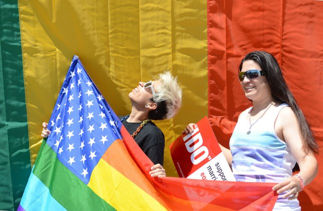 People pose for pictures in front of a rainbow flag that was hung in honor of the U.S. Supreme Court's decision legalizing gay marriage in June 2015. San Francisco artist Gilbert Baker, who created the rainbow flag as a symbol for the LGBT community died at age 65 on Friday. Photo by Terry Schmitt/UPI