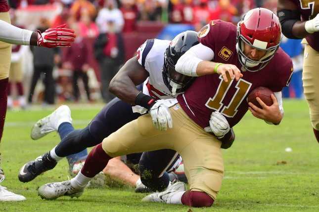 Washington Redskins quarterback Alex Smith (11) is sacked by Houston Texans outside linebacker Jadeveon Clowney (90) in the fourth quarter on Sunday at FedEx Field in Landover, Maryland. Photo by Kevin Dietsch/UPI