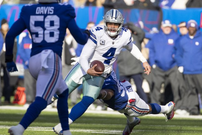 Dallas Cowboys quarterback Dak Prescott (4) scrambles while under pressure by New York Giants middle linebacker B.J. Goodson in the first quarter on Sunday at MetLife Stadium in East Rutherford, New Jersey. Photo by Chris Szagola/UPI