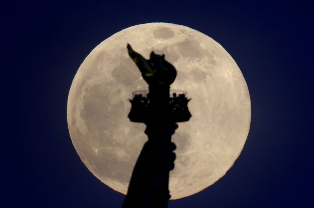 A pink supermoon rises behind the Statue of Liberty from Liberty State Park in Hoboken, N.J., on April 26. The final supermoon of the year will appear Thursday. Photo by John Angelillo/UPI