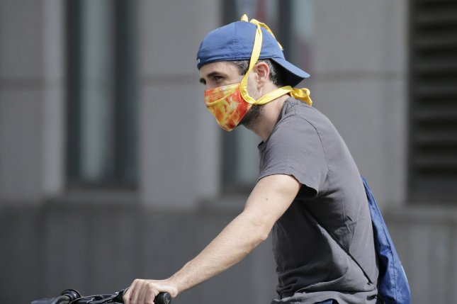 A man wears a protective face mask while riding a bicycle on the Upper West Side of Manhattan on Wednesday in New York City as the COVID-19 pandemic continues. Photo by John Angelillo/UPI