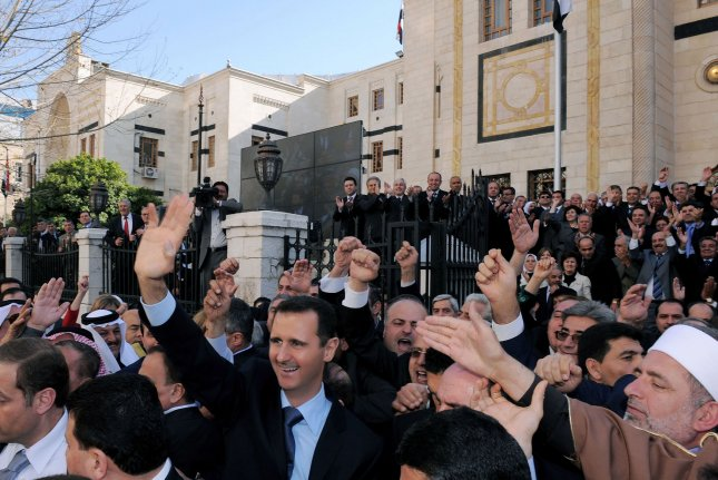Syrian President Bashar al-Assad waves to supporters in the street after addressing parliament on March 30, 2011 in Damascus, Syria. UPI